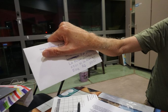 """Tony Fines holds a letter addressed to the husband of a migrant recently arrived at Casa Alitas. The couple were separated during their journey, and the husband is being held at a detention facility in Eloy. """"The biggest gift anybody can receive in these places is a letter from the outside,"""" Fines told the wife. (Photo by Taylor O'Connor/Cronkite Borderands Project)"""