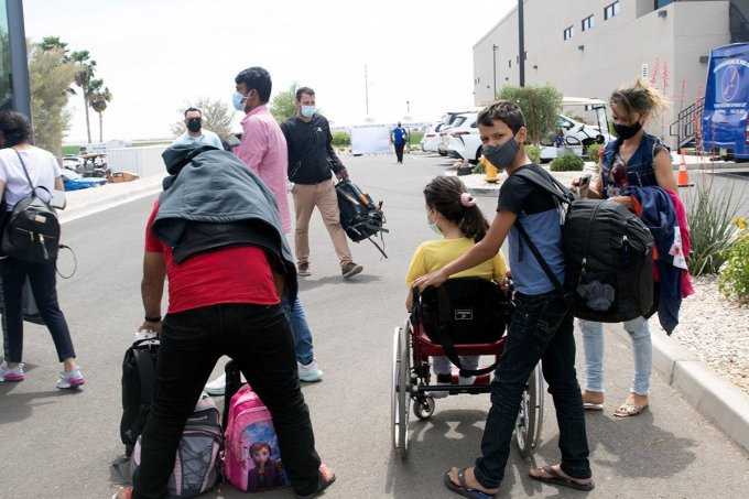A family waits to board the bus to take them to a Tucson shelter, where volunteers will try to contact relatives in the U.S. who might sponsor the asylum seekers. (Photo by Kamilah Williams/Cronkite Borderlands Project)