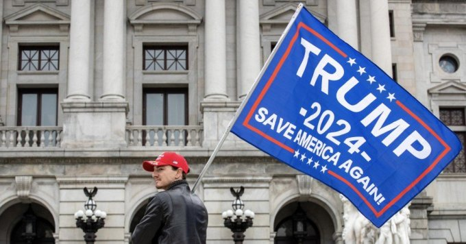A protester holds a Trump 2024 flag in front of the Pennsylvania State Capitol on February 27, 2021. (Photo: Paul Weaver/SOPA Images/LightRocket via Getty Images)