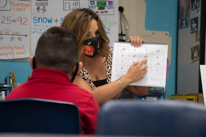 Sandra Cobos, an acceleration specialist at Justine Spitalny School in Phoenix, guides children through a series of vocalization exercises. Cobos helps students who struggled with online learning to catch up with their studies. (Photo by Mingson Lau/Cronkite News)