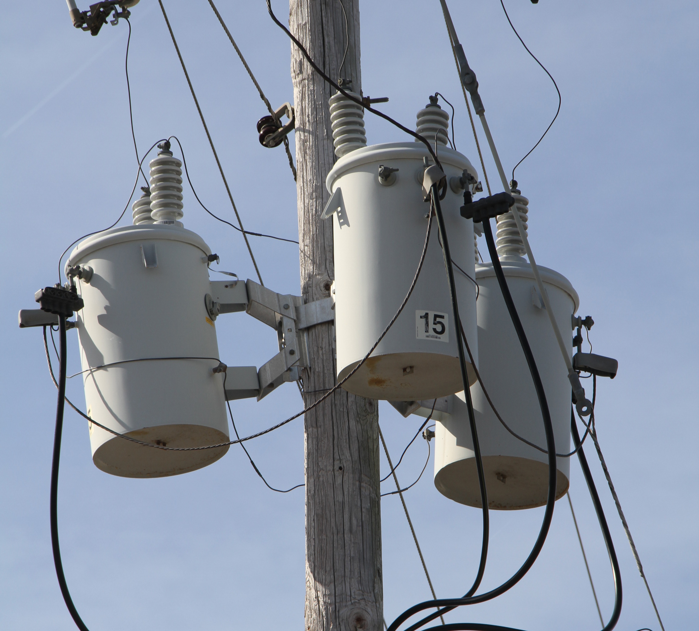 Three White Distribution Transformers On Pole With Light