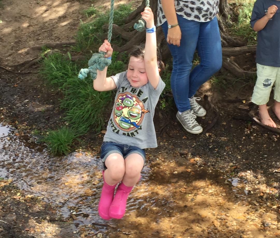 Girl swinging on rope over stream
