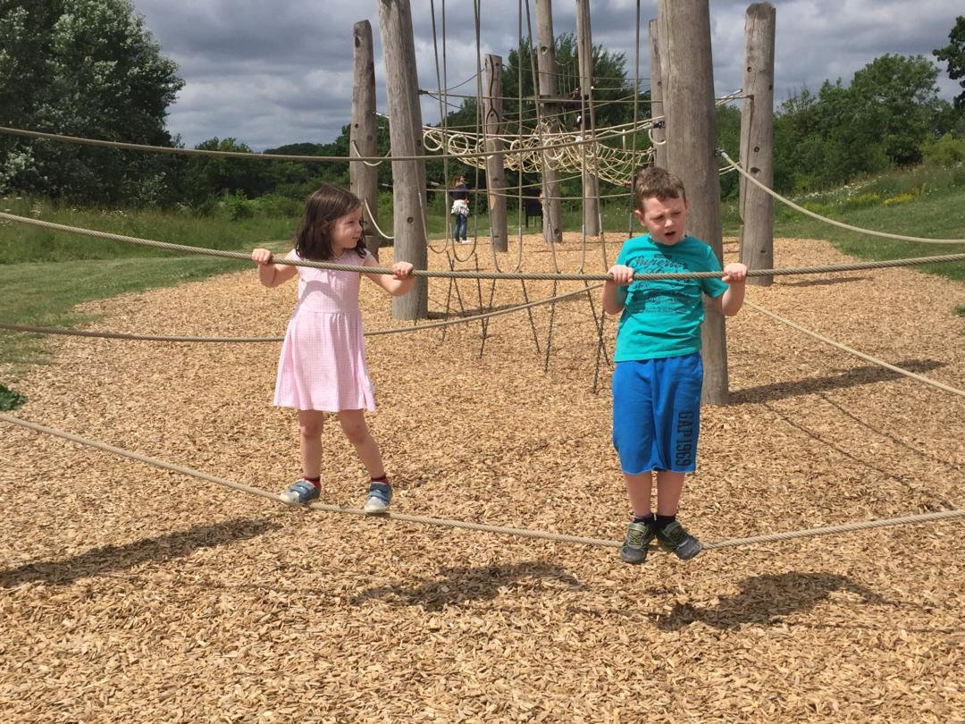 Five ways to introduce free range parenting in day to day life - Boy and girl climbing across a rope.
