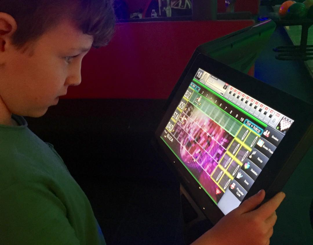 Child using the screen at rollerbowl
