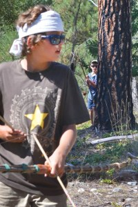 "Lucaas Gonzalez-Ortega, of Carlton, stayed alert during a game of ""Hunger Games, Battle to the Death"" (played with handmade bows and foam-tipped arrows), but didn't know he was about to be ambushed by fellow warrior Peter Sawyer Walter of Brooklyn, NY. Kids at the four-day Warrior Camp, taught by primitive skills instructors Katie Russell and Ex Umbra, also fashioned atlatls (throwing sticks) out of mullein stalks; learned to make friction fire; caught, roasted and ate grasshoppers; practiced stalking and wilderness movement; played games and learned other warrior skills. Photo by Laurelle Walsh"