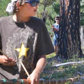 """Lucaas Gonzalez-Ortega, of Carlton, stayed alert during a game of """"Hunger Games, Battle to the Death"""" (played with handmade bows and foam-tipped arrows), but didn't know he was about to be ambushed by fellow warrior Peter Sawyer Walter of Brooklyn, NY. Kids at the four-day Warrior Camp, taught by primitive skills instructors Katie Russell and Ex Umbra, also fashioned atlatls (throwing sticks) out of mullein stalks; learned to make friction fire; caught, roasted and ate grasshoppers; practiced stalking and wilderness movement; played games and learned other warrior skills. Photo by Laurelle Walsh"""