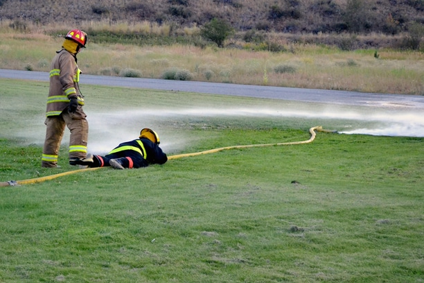 """District 6 volunteers practice a """"wild hose"""" drill during training. Photo by Laurelle Walsh"""