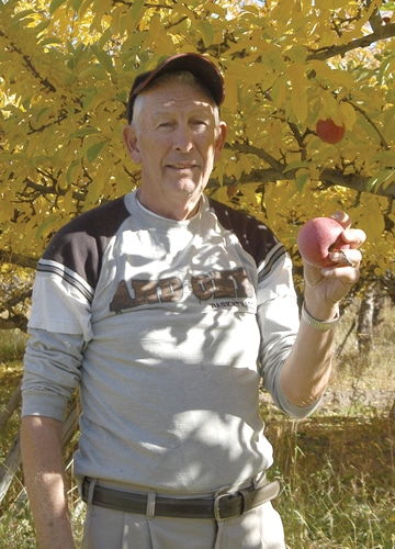 "Dave Schulz holds an apple from what he says is the ""worst"" harvest he's seen. Photo by Ann McCreary"