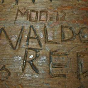 """Over the years, patrons laboriously carved names, designs and messages into the wooden bar top of Antlers Saloon and Cafe, where remembrances of long-gone hunting friends like """"Waldo Red"""" remain. Photo by Mike Maltais"""