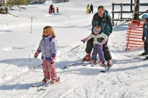 Mark Roman, Winthrop, with daughters Audrey, front, and Camille, tries out the rope tow during the first full weekend of skiing at the Loup Loup Ski Bowl. Roman was giving 3-year-old Camille her first taste of skiing. Audrey, 5, has been skiing for two years. Photo by Mike Maltais