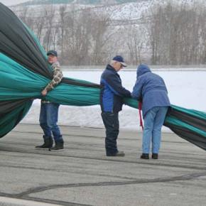 Steve Justice (left), second crew chief and brother of pilot Dale Justice, center, and crew chief Mary Heath beginning to work the air out of the Outer Limits balloon. Photo by Darla HusseyPhoto by Darla Hussey