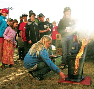 """Hanna Bakke, center, takes her """"fire tornado"""" sixth-grade fire experiment out for a spin at the Methow Valley Elementary School Science Fair last Thursday. Partner Willow Temple, standing with cup, is prepared with a bit of water if things should go awry. Hannah and Willow are in the sixth grade.   Photo by Darla Hussey"""