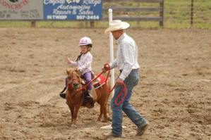 A tiny pole bender from Pasco waves to the crowd as she completes the course with a little help at the 43rd annual Methow Valley Memorial Day Rodeo last weekend. Photo by Mike Maltais