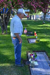 Carl Miller lays a bouquet of lilacs on the grave of a Dammann relative. Photo by Laurelle Walsh