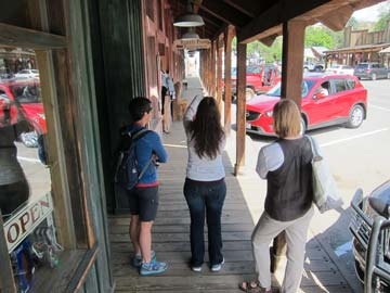 Kristen Smith, left, Winthrop Chamber of Commerce marketing manager, and Paula Christen look on as Krys Karns of Washington Filmworks gets a shot on Riverside Avenue. Photo by Don Nelson