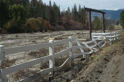 A fence that melted in the fire surrounds a Benson Creek pasture now buried in mud by last week's slide. Photo by Ann McCreary
