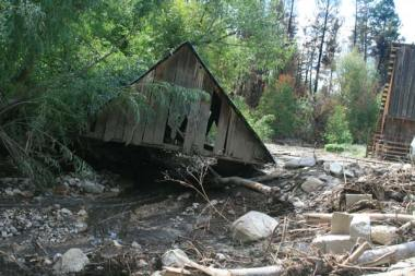 Kim and Lenore Maltais, whose home was destroyed in the wildfire a month ago, lost a 100-year old storage building when the force of the creek ripped it off its foundation and carried it hundreds of feet downstream. Photo by Marcy Stamper, Methow Valley News