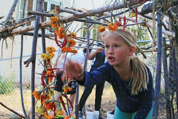 Photos by Marcy Stamper Susannah Bacon explored the Community School's fort, which is adorned with garlands of dried flowers and peppers.