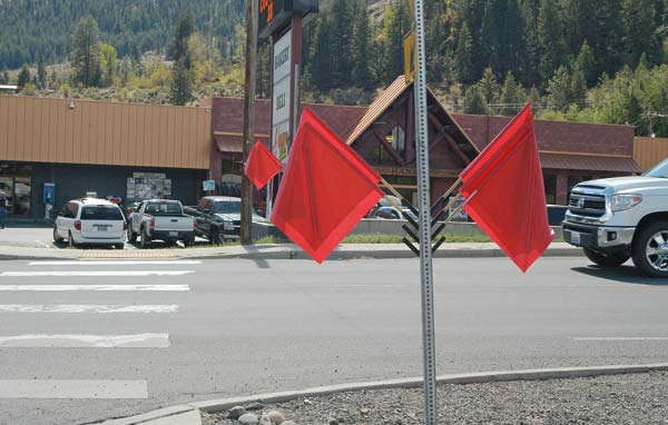 Photo by Ann McCreary New pedestrian safety flags at a crosswalk next to Hank's Harvest Foods were back in place Tuesday afternoon (Aug. 23) after they were recovered from a clothing donation bin next to the grocery store. Stealing the flags is a criminal offense, Twisp officials warn.