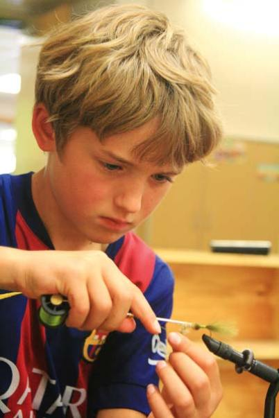 Photo by Marcy Stamper Second-grader Ben Kaufman concentrates on tying his first fly in the fly fishing club.