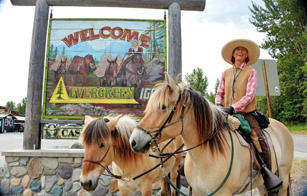 Photo by Kristen Smith While riding through Winthrop, Bernice Ende pauses before the painted Evergreen grocery store sign, which includes a woman who looks remarkably like Ende.