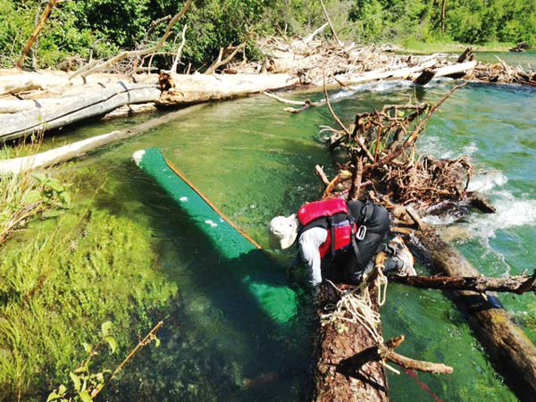 Photo courtesy of David Clement and Betsy Weiss David Clement retrieves his canoe from a log jam on the Methow River.