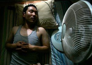 A man lies next to an electric fan in his home in Seoul July 4, 2007. Summertime in South Korea means cold beer on steamy nights and lonely deaths in stuffy rooms blamed on electic fans. Electric fans and Koreans are a deadly combination, according to an urban legend in the country that has it if a person sleeps in a closed room with a fan on all night they may never wake up. To match feature KOREA-FANS/ REUTERS/Han Jae-Ho (SOUTH KOREA)