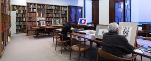 study drawings research prints libraries library background drawing narrow centers table dark wood shelves looking books