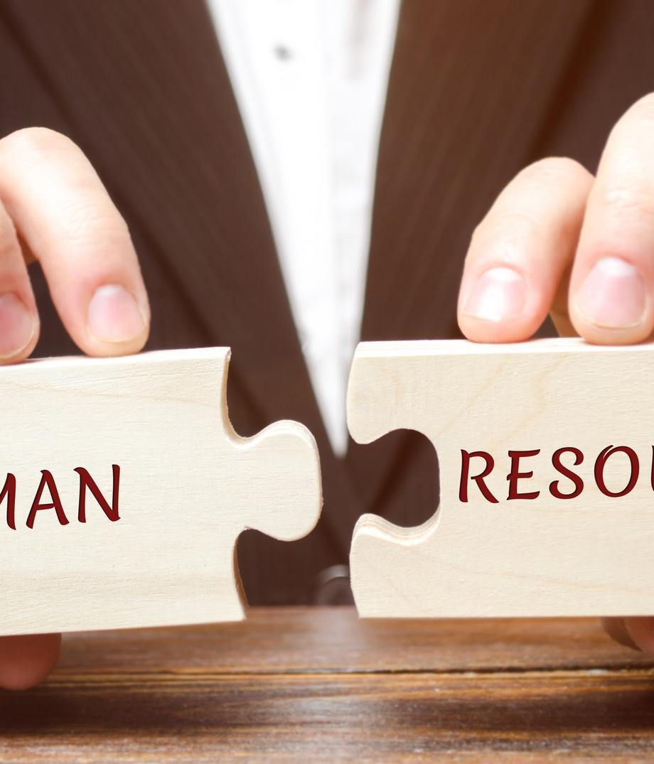 Businessman collects wooden puzzles with the word Human resources