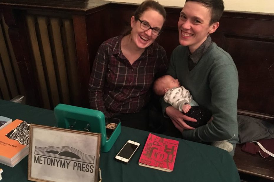 Two adults lean cheeks towards each other, smiling, and one of them holds a small sleeping baby. A framed Metonymy Press sign, a cashbox, a box, a notebook, and a phone are on the table in front of them.