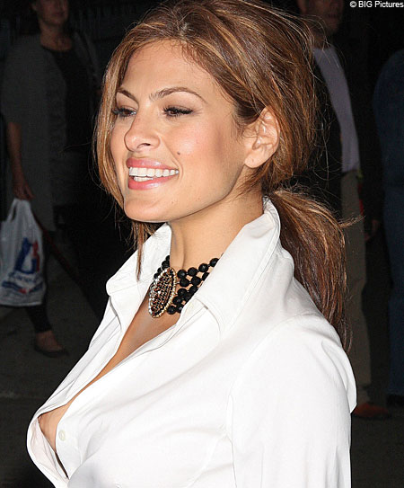 A smiling Eva Mendes seems oblivious to her wardrobe malfunction