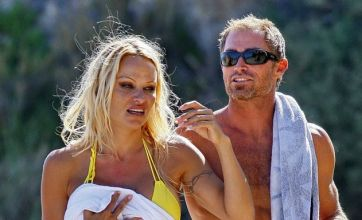'Pamela Anderson and scuba diver on the rocks'