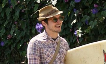 Elijah Wood takes his surf board on a walk