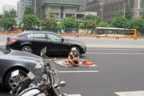 Keeping calm: The yoga fan sets up camp in the middle of the road