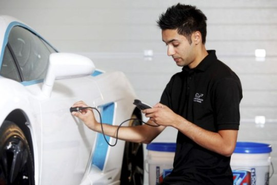 Attention to detail: Gurcharn Sahota uses an electronic meter to check the depth of the car's paintwork, right, before using a lightgun to look for any minute scratches Picture: SWNS