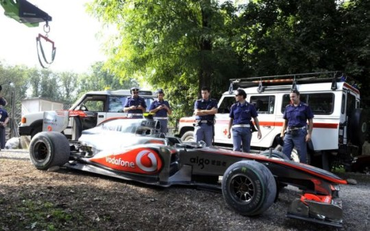 Gritty drama: Lewis Hamilton's McLaren is guarded by police after being forced onto the gravel at Monza (Action Images)