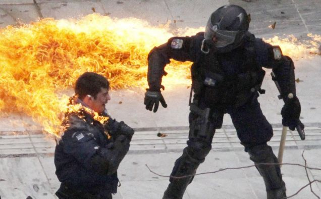 A policeman is set alight during the riots in Athens (AP)
