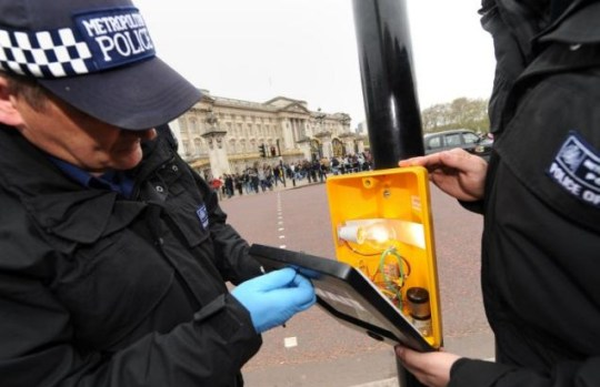 Metropolitan Police officers carry out security checks on traffic lights along the Mall. 5,000 officers will be on duty for the royal wedding on Friday (Getty)