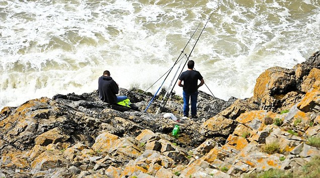 People fish at a place known locally as 'Blue Pool' near Llangennith