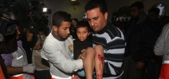 A Palestinian man carries an injured child