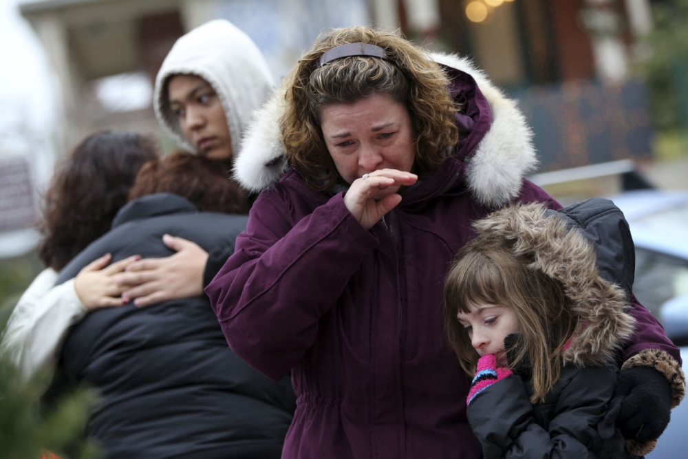 A town in tears: Mourners at one of the makeshift memorials for the children and adults who died at the hands of gunman Adam Lanza (Picture: AP)