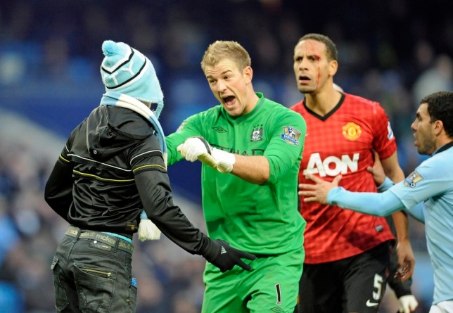 Manchester City goalkeeper Joe Hart (C) shouts at a City fan (L) who ran onto the pitch as Manchester United's Rio Ferdinand