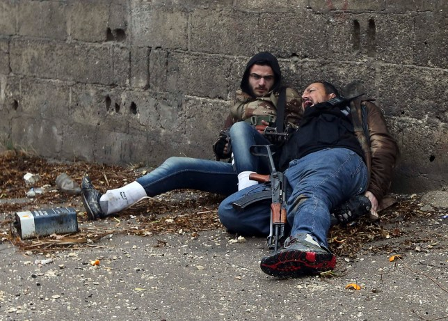 A Free Syrian Army fighter looks at his comrade as he gets shot by sniper fire