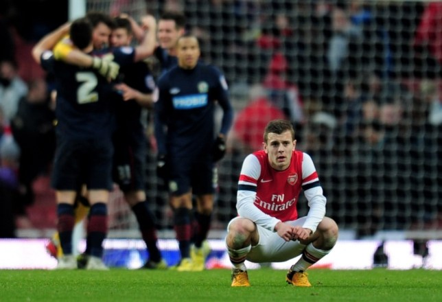 Jack Wilshere looks dejected as Blackburn celebrate a famous victory