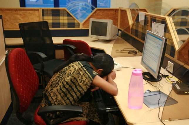 A tutor falls asleep on her desk at TutorVista headquarters