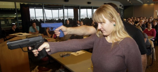FILE - In this Dec. 27, 2012, file photo, Joanna Baginska, a fourth-grade teacher from Odyssey Charted School, in American Fork, Utah, aims a 40 cal. Sig Sauer as Clark Aposhian, president of Utah Shooting Sport Council, demonstrates with a plastic gun, rear, during concealed-weapons training for the teachers in West Valley City, Utah. Legislators alarmed by the prospect of armed teachers in classrooms are proposing a counter-measure: The teachers would have to disclose they're packing to parents, who could have their children reassigned to another class. Gun lobbyists say the promised legislation runs counter to common sense because privacy is a cornerstone of having a permit to conceal a weapon. Utah allows teachers to pack guns in classrooms, and more teachers are applying for the permit. (AP Photo/Rick Bowmer, File)