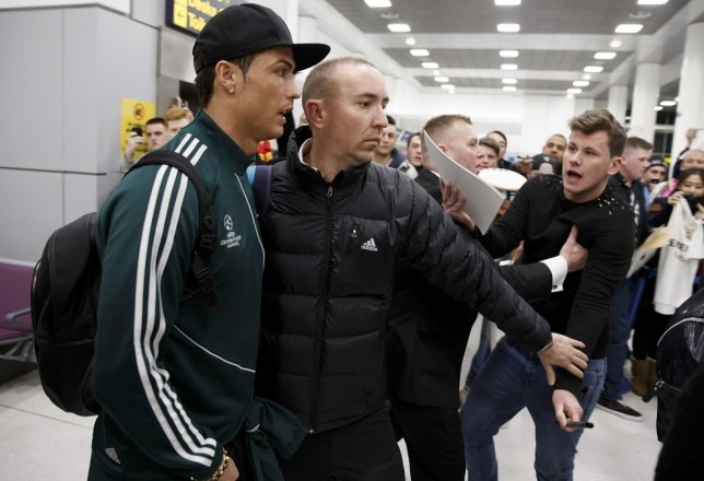 He's here: Ronaldo makes his way through the fans at Manchester airport (Picture: Getty)