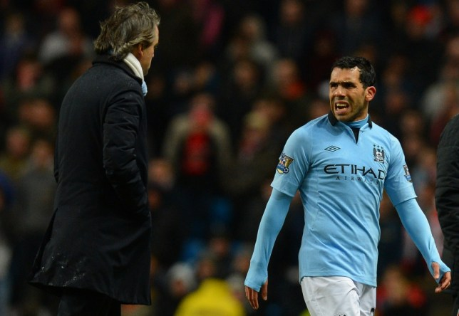 Manchester City's Argentinian forward Carlos Tevez (R) speaks to Manchester City's Italian manager Roberto Mancini (L) after being substituted during the English FA Cup quarter-final football match between Manchester City and Barnsley at the Etihad Stadium in Manchester, north-west England, on March 9, 2013. Manchester City won 5-0. AFP PHOTO/ANDREW YATES RESTRICTED TO EDITORIAL USE. No use with unauthorized audio, video, data, fixture lists, club/league logos or ìliveî services. Online in-match use limited to 45 images, no video emulation. No use in betting, games or single club/league/player publications.ANDREW YATES/AFP/Getty Images