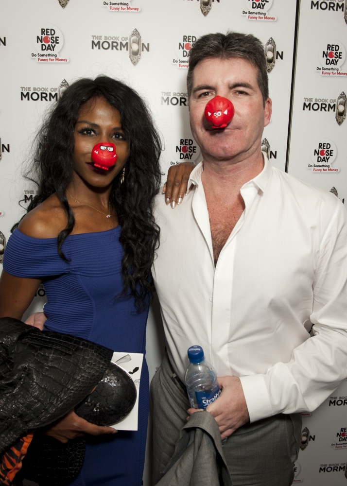 Simon Cowell shows his comical side by wearing a red nose as he cuddles up to Sinitta