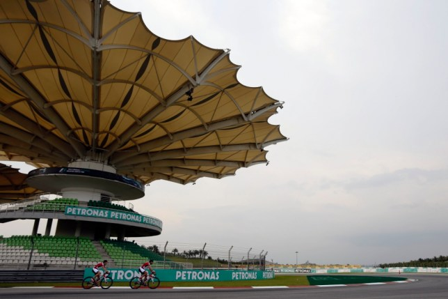 Ferrari Formula One driver Fernando Alonso (L) of Spain rides his bicycle around the Sepang International Circuit, ahead of the Malaysia F1 Grand Prix in Sepang March 20, 2013.  REUTERS/Tim Chong (MALAYSIA - Tags: SPORT MOTORSPORT F1)